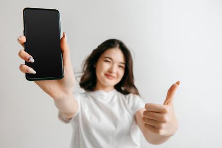 Ritratto di una ragazza asiatica casuale sicura che mostra lo schermo in bianco del telefono cellulare isolato sopra fondo grigio allo studio.