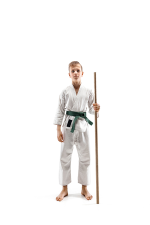 Teen boy fighting with wooden sword at Aikido training in martial arts school. Healthy lifestyle and sports concept. Fightrer in white kimono on white background. Karate man in uniform.