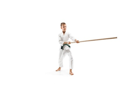 Teen boy fighting with wooden sword at Aikido training in martial arts school. Healthy lifestyle and sports concept. Fightrer in white kimono on white background. Karate man in uniform. Stock Photo - 118754177