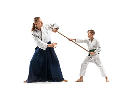 Man and teen boy fighting with wooden sword at Aikido training in martial arts school. Healthy lifestyle and sports concept. Fightrers in white kimono on white background. Karate men in uniform.