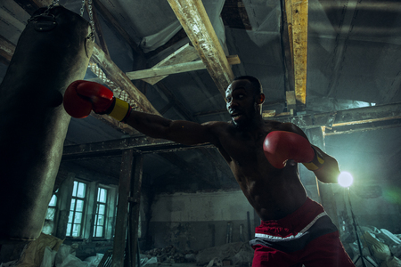 Hands of boxer over dark gym background. Strength, attack and motion concept. Fit african american model in movement. Naked muscular athlete in red gloves. Sporty man during boxing.