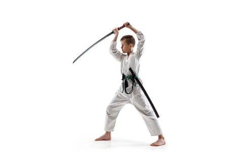 Teen boy fighting at Aikido training in martial arts school. Healthy lifestyle and sports concept. Fightrer in white kimono on white background. Karate man with concentrated face in uniform. Stock Photo