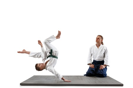 Man and teen boy fighting at Aikido training in martial arts school. Healthy lifestyle and sports concept. Fightrers in white kimono on white background. Karate men with concentrated faces in uniform. Banque d'images - 118952708