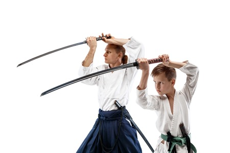 Man and teen boy fighting at Aikido training in martial arts school. Healthy lifestyle and sports concept. Fightrers in white kimono on white background. Karate men with concentrated faces in uniform. Banque d'images - 118952714