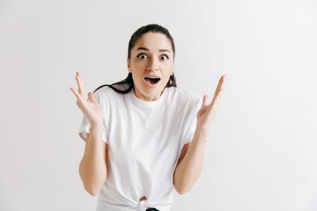 Ik won. Winnende succes gelukkige vrouw die een winnaar viert. Dynamisch beeld van vrouwelijk model op grijze studioachtergrond. Overwinning, verrukkingsconcept. Menselijk gezicht emoties concept.