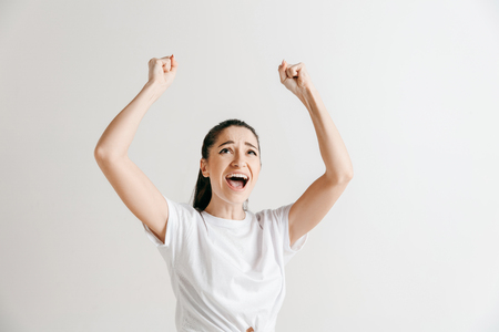 I won. Winning success happy woman celebrating being a winner. Dynamic image of female model on gray studio background. Victory, delight concept. Human facial emotions concept.