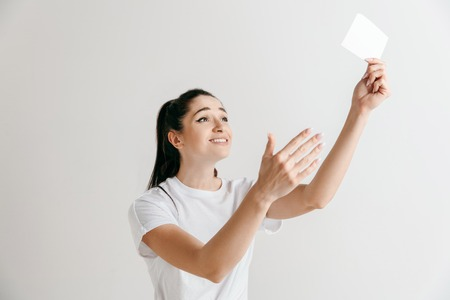 Young woman with a surprised happy expression won a bet on studio background. Human facial emotions and betting concept. Trendy colors Stock Photo