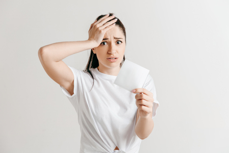 Young woman with a surprised unhappy expression lost a bet on studio background. Human facial emotions and betting concept. Trendy colors. Stock Photo