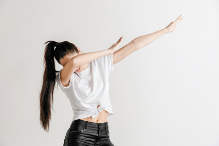 Young woman makes a dab movement with arms on a gray background. Human emotions, facial expression concept.