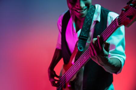 Afroamerikanischer hübscher Jazzmusiker, der im Studio auf Neonhintergrund Bassgitarre spielt. Musikkonzept. Junger fröhlicher attraktiver Kerl improvisiert. Nahaufnahme Retro-Porträt. Standard-Bild