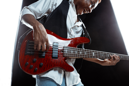 African American handsome jazz musician playing bass guitar in the studio on a black background. Music concept. Young joyful attractive guy improvising. Close-up retro portrait. Reklamní fotografie