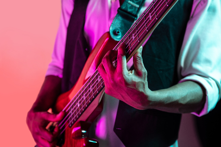 African American handsome jazz musician playing bass guitar in the studio on a neon background. Music concept. Young joyful attractive guy improvising. Close-up retro portrait. Banque d'images - 118952939