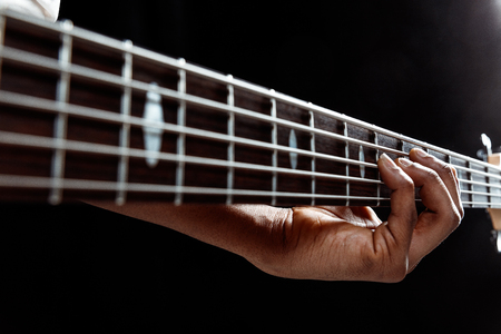African American handsome jazz musician playing bass guitar in the studio on a black background. Music concept. Young joyful attractive guy improvising. Close-up retro portrait. Banque d'images - 118952966