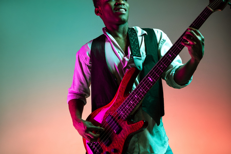 African American handsome jazz musician playing bass guitar in the studio on a neon background. Music concept. Young joyful attractive guy improvising. Close-up retro portrait. Banque d'images - 118952967