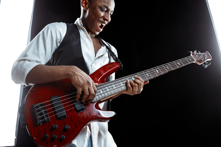 African American handsome jazz musician playing bass guitar in the studio on a black background. Music concept. Young joyful attractive guy improvising. Close-up retro portrait. Foto de archivo