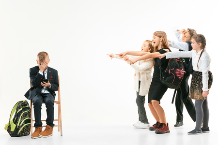 Little boy sitting alone on chair and suffering an act of bullying while children mocking. Sad young schoolboy sitting on studio against white background.