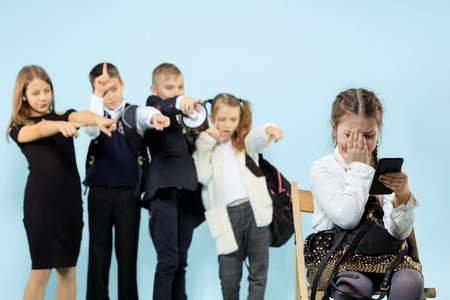 Little girl sitting alone on chair and suffering an act of bullying while children mocking. Sad young schoolgirl sitting on studio against blue background.
