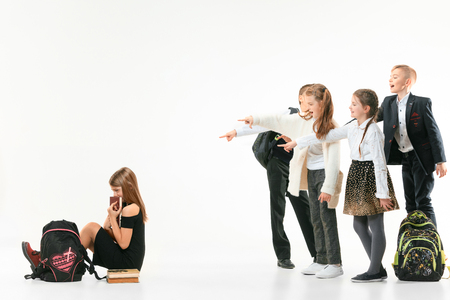 Little girl sitting alone on floor and suffering an act of bullying while children mocking. Sad young schoolgirl sitting on studio against white background.