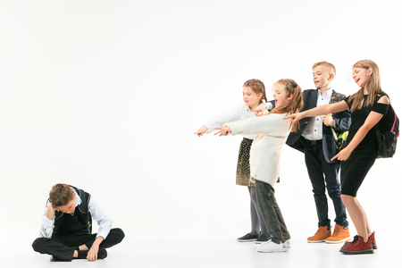 Little boy sitting alone on floor and suffering an act of bullying while children mocking in the background. Sad young schoolboy sitting on studio against white background. Stock Photo
