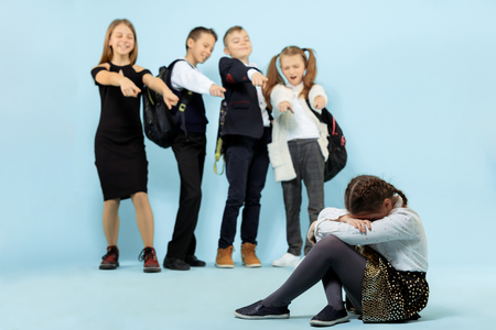 Little girl sitting alone on floor and suffering an act of bullying while children mocking. Sad young schoolgirl sitting on studio against blue background.