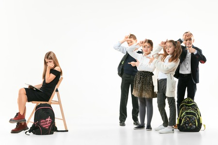 Little girl sitting alone on chair and suffering an act of bullying while children mocking. Sad young schoolgirl sitting on studio against white background. Stock Photo