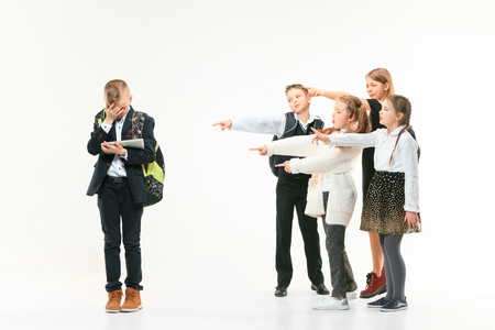 Little boy standing alone and suffering an act of bullying while children mocking in the background. Sad young schoolboy standing on studio against white background.