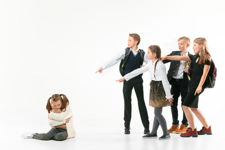 Klein meisje zit alleen op de vloer en lijdt aan pesterijen terwijl kinderen spotten. Triest jonge schoolmeisje zittend op studio tegen een witte achtergrond. Stockfoto