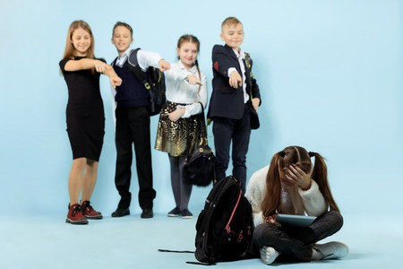 Little girl sitting alone on floor and suffering an act of bullying while children mocking. Sad young schoolgirl sitting on studio against blue background. 写真素材 - 119204289