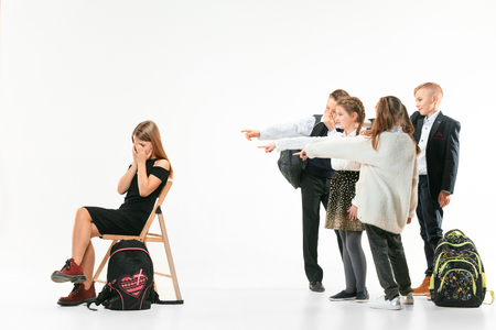 Little girl sitting alone on chair and suffering an act of bullying while children mocking. Sad young schoolgirl sitting on studio against white background. 写真素材