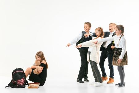 Klein meisje zit alleen op de vloer en lijdt aan pesterijen terwijl kinderen spotten. Triest jonge schoolmeisje zittend op studio tegen een witte achtergrond.
