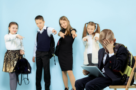 Little boy sitting alone on chair and suffering an act of bullying while children mocking. Sad young schoolboy sitting on studio against blue background.