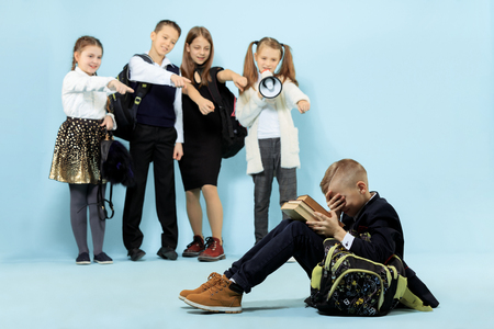 Little boy sitting alone on floor and suffering an act of bullying while children mocking. Sad young schoolboy sitting on studio against blue background.