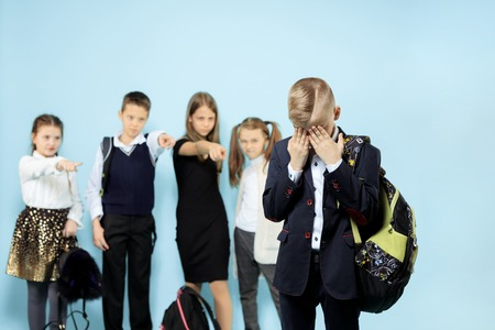 Little boy standing alone and suffering an act of bullying while children mocking in the background. Sad young schoolboy standing on studio against blue background. Stockfoto