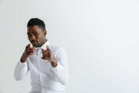 Afro american man over isolated grey background pointing with finger to the camera and to you, hand sign, positive and confident gesture from the front