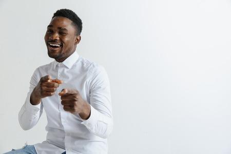 Hombre afroamericano sobre fondo gris aislado apuntando con el dedo a la cámara y a usted, signo de la mano, gesto positivo y seguro desde el frente