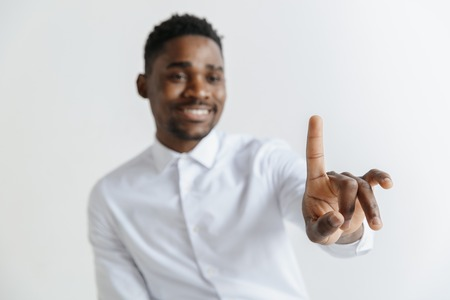 Handsome businessman pointing his finger to the camera and slicking virtual image or text, finger is in focus while his face is out of focus. Shallow depth of field. Young african american guy interacts with empty space. Negative space to insert your text or image.