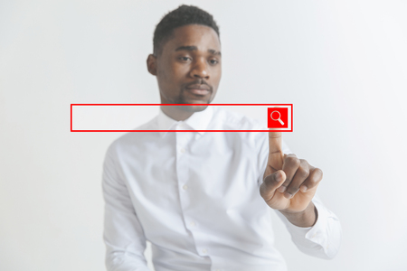 Handsome businessman pointing his finger to the camera and slicking virtual button, finger is in focus while his face is out of focus. Shallow depth of field. Young african american guy interacts with empty search bar. Negative space to insert your text. Reklamní fotografie