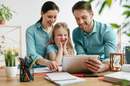 Father, mother and their daughter are smiling while spending time together. A day with family. Young happy couple with child are watching something funny on the tablet. Education, studying and knowledge sharing concept.