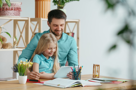Father and his daughter are smiling while spending time together. A day with family. Young pretty girl and her dad are studying with tablet. Education, studying and knowledge sharing concept. Banque d'images - 119205721