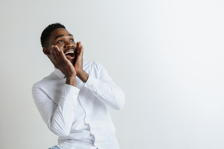 Portrait of excited young African American male screaming in shock and amazement. Surprised black hipster looking impressed, cant believe his own luck and success