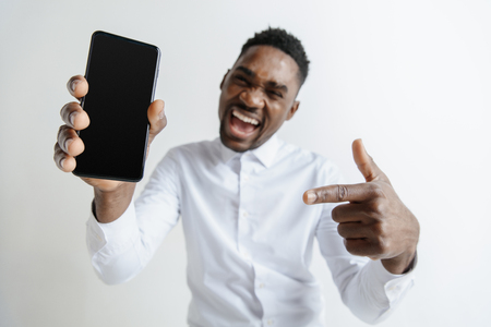 Indoor portrait of attractive young black african man isolated on grey background, holding blank smartphone, smiling at camera, showing screen, feeling happy and surprised. Human emotions, facial