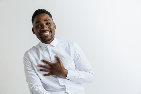 Grateful happy pleased african man holding hands on chest to heart feeling love appreciation gratitude honesty, thankful sincere proud black guy thanking isolated on white studio background. Stok Fotoğraf - 119324696