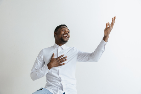 Grateful happy pleased african man holding hands on chest to heart feeling love appreciation gratitude honesty, thankful sincere proud black guy thanking isolated on white studio background.