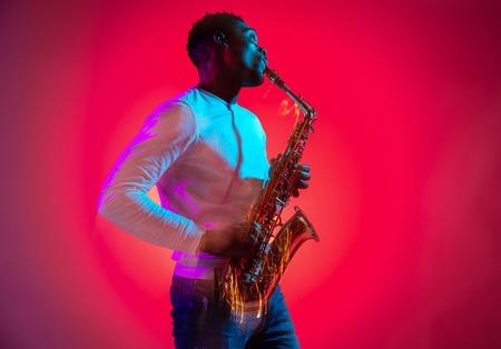 Beau musicien de jazz afro-américain jouant du saxophone en studio sur fond néon. Notion de musique. Jeune mec séduisant et joyeux improvisant. Portrait rétro gros plan.
