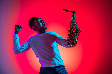 African American handsome jazz musician interacts with audience and holding the saxophone in the studio on a neon background. Music concept. Young joyful attractive guy improvising. Close-up retro por