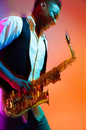African American handsome jazz musician playing the saxophone in the studio on a neon background. Music concept. Young joyful attractive guy improvising. Close-up retro portrait. Banque d'images