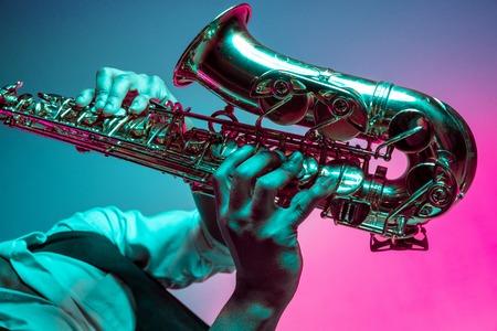 Afro-Amerikaanse knappe jazzmuzikant die saxofoon speelt in de studio op een neonachtergrond. Muziekconcept. Jonge vrolijke aantrekkelijke kerel improviseren. Close-up retro portret.