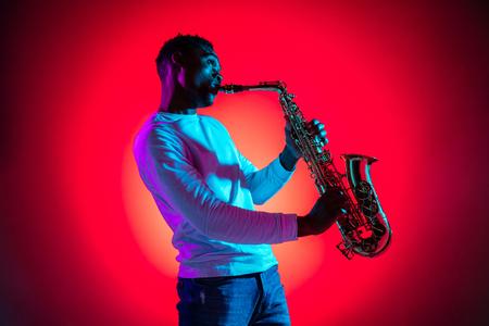 Beau musicien de jazz afro-américain jouant du saxophone en studio sur fond néon. Notion de musique. Jeune mec séduisant et joyeux improvisant. Portrait rétro gros plan. Banque d'images