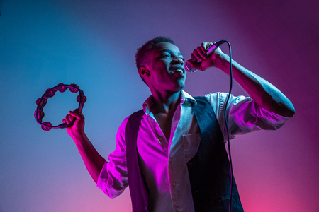 African American handsome jazz musician playing tambourine and singing into the microphone in the studio on a neon background. Music concept. Young joyful attractive guy improvising. Close-up retro portrait.