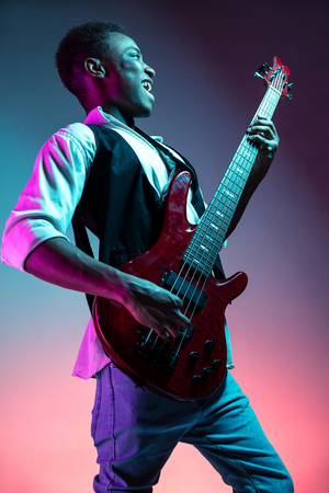 African American handsome jazz musician playing bass guitar in the studio on a neon background. Music concept. Young joyful attractive guy improvising. Close-up retro portrait. Banque d'images - 119324853